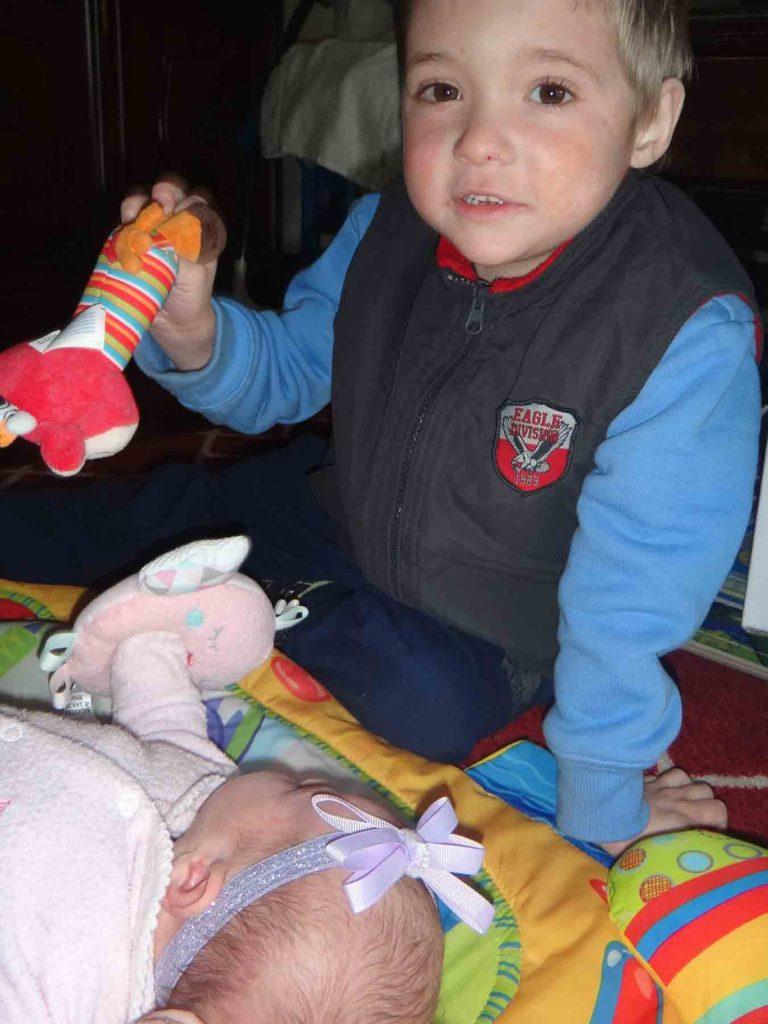 https://www.writteninwaikiki.com/three-becomes-four-dealing-new-sibling/ kids siblings baby toddler playing