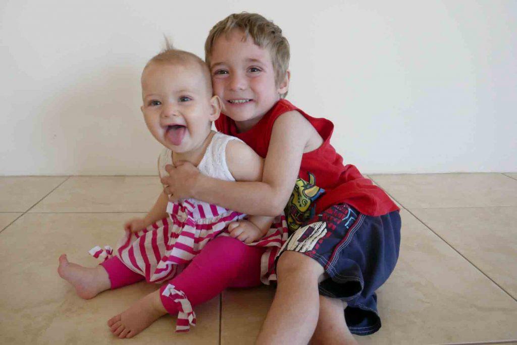 https://www.writteninwaikiki.com/three-becomes-four-dealing-new-sibling/ kids siblings hugs