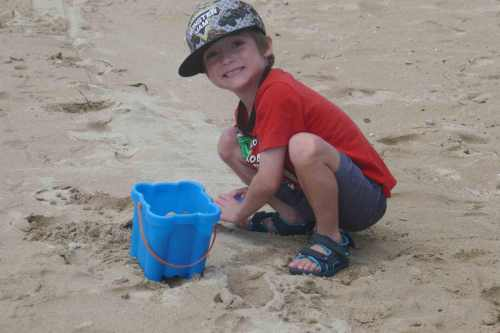 how to build self-esteem in kids boy child playing in sand at the beach