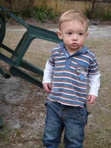 boy toddler standing next to a fallen chair