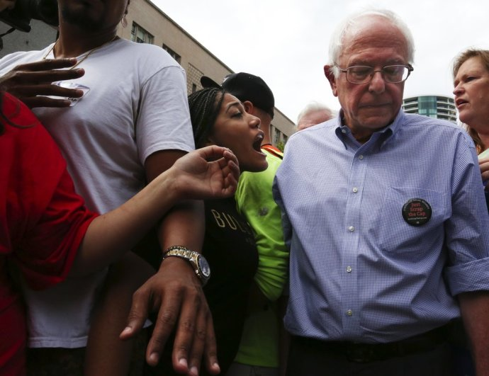"""Democratic presidential candidate Sen. Bernie Sanders, I-Vermont, is confronted on the Westlake Park stage by Mara Jacqueline Willaford CQ over """"Black Lives Matter"""" issues.  She and another activist took over the rally at this point leading to the Senator leaving the stage, making his way through the crowd which thanked him for coming, and getting in a car and being driven away. Saturday August 8 2015,"""