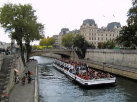 Tłumy turystów na statku wycieczkowym na Sekwanie spoglądają na Notre-Dame