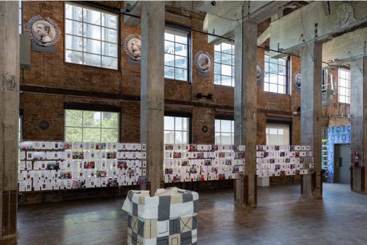 """Installation view of 'Of the People' featuring Sheryl Oring's """"I Wish to Say"""" (2016). consisting of note cards suspended between pillars (Photo by Etienne Frossard, courtesy of the artists and Smack Mellon)"""
