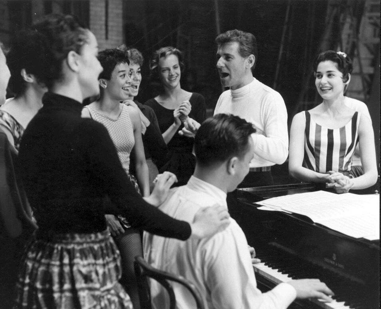 Bernstein at rehearsal for West Side Story. Carol Lawrence (who played Maria) is at his left, and lyricist Stephen Sondheim is playing the piano, 1957