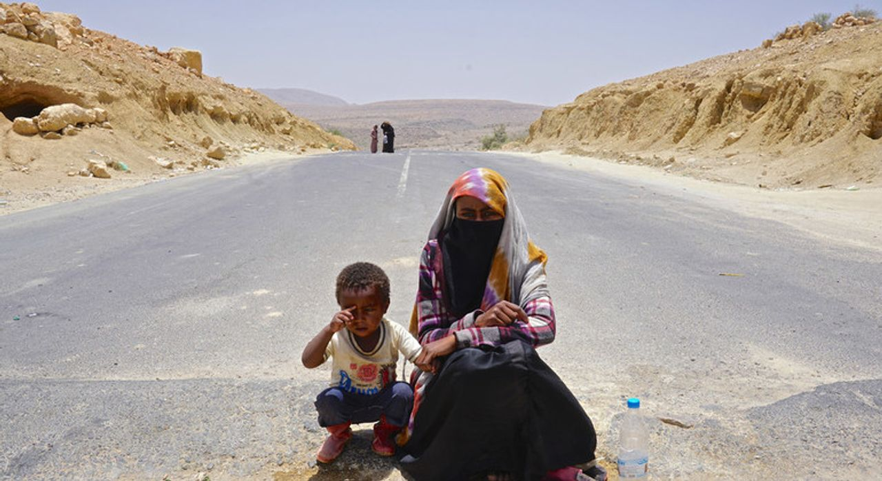 Suad, aged 18, begs in the middle of the road between Yemens capital, Sanaa, and Saada with her four-year-old nephew, whose mother was killed by the Saudi war on Yemen - Credit: Giles Clarke/United Nations Office for the Coordination of Humanitarian Affairs (OCHA)