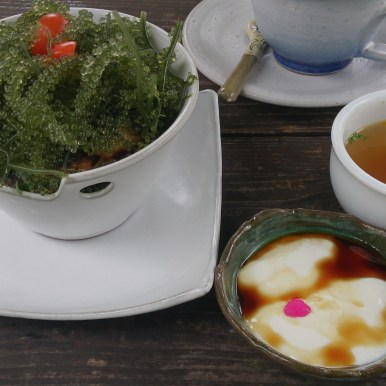"Okinawan dish of ""forbidden "" or black rice and white rice, with braised pork and sea grapes. Bone broth soup with scallions. Tofu with peanut sauce and hibiscus tea."