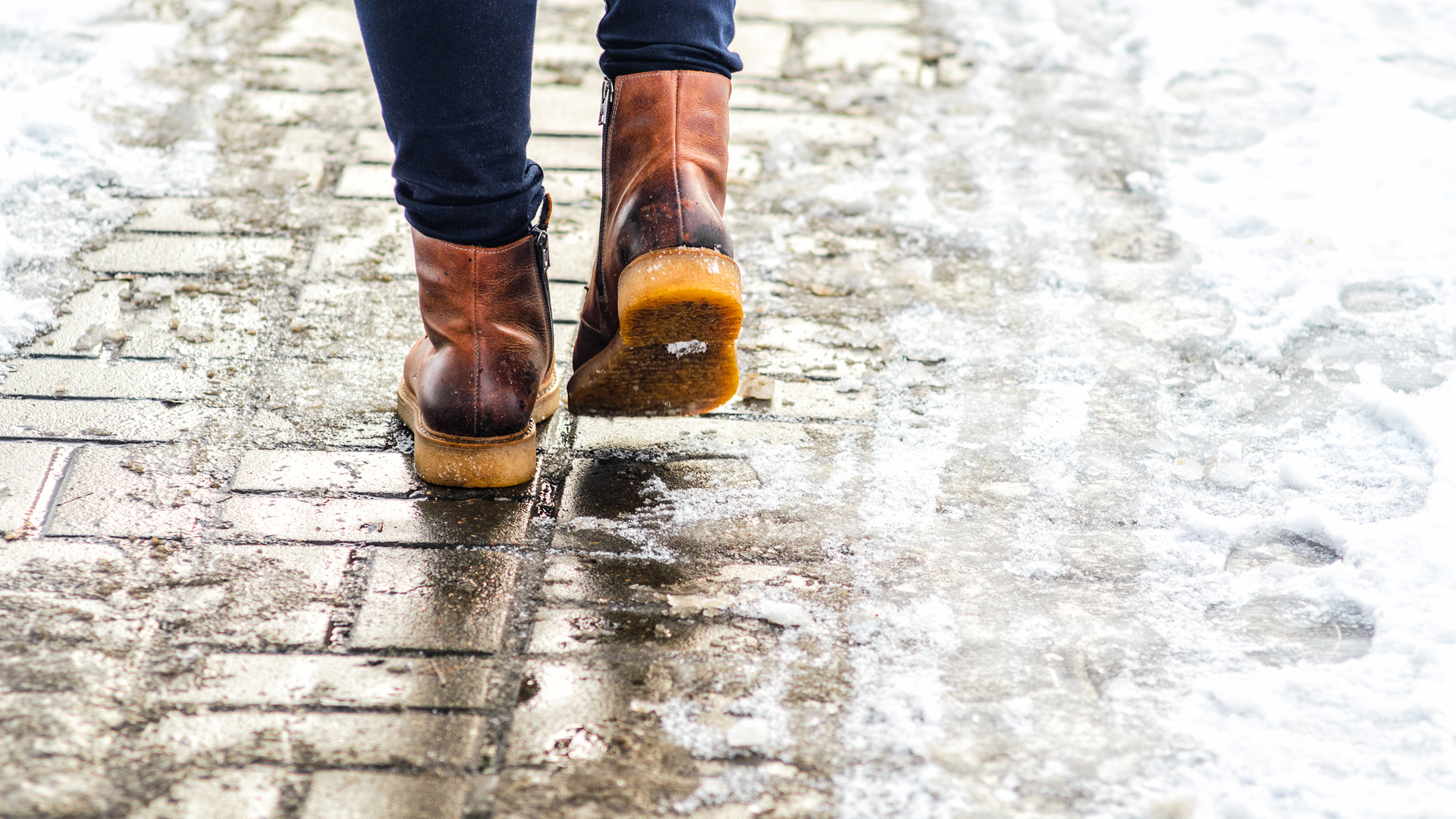 Walk On Wet Melted Ice Pavement. Back View On The Feet Of A Man _1548781800781