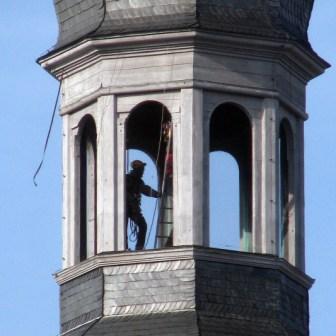 Zufallstreffer: In luftiger Höhe arbeiten hier zwei angeseilte Arbeiter auf dem höchsten Punkt des Kirchturms von Stift Haug.