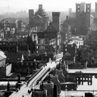 """Die nach dem Bombenangriff vom 16. März zerstörte Würzburger Altstadt - Ansicht vom April 1945. Nach dem Einmarsch der US-Amerikaner wurde die zerstörte Alte Mainbrücke mit einer so genannten """"Bailey Bridge"""" (= Behelfsbrücke) passierbar gemacht."""