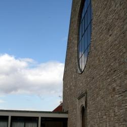 Wolken spiegeln sich im großen Lichtfenster der Kirche.