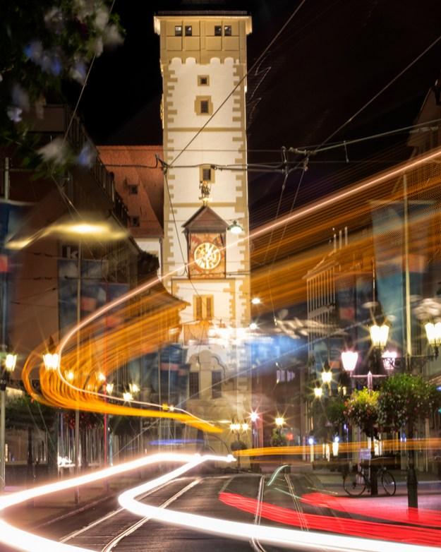 Eine Straßenbahn fährt bei Nacht durch die Augustinerstraße. Im Hintergrund das Würzburger Rathaus mit dem Grafeneckart.