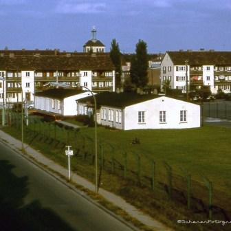 Diese ehemaligen Baracken wurden schon vor vielen Jahren entfernt. Inzwischen steht auf der Fläche ein neues Jugendzentrum für den Stadtteil Zellerau. Die langen Schatten auf der Straße lassen die ehemaligen Gebäude auf dem Gelände erahnen die auch schon lange abgerissen sind.