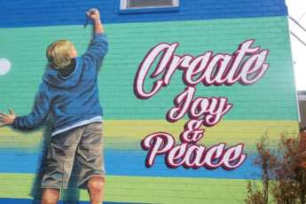 "painting on brick of a boy drawing saying ""Create Joy and Peace"""