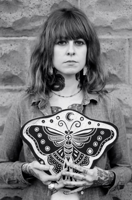 Bryn Perrott holding a piece with a butterfly