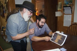 two men discussing data printed on a piece of paper