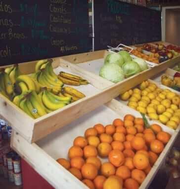 Insdie a fruit stand showing fresh bananas, oranges, lemons, lettuce, etc.