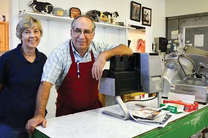 Ralph and Janet Richmond standing near a meet slicer