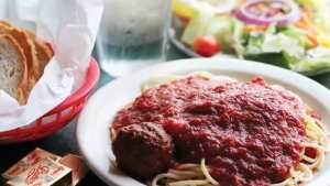 A plate of spaghetti with a meatball.