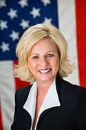 Judy McCauley in front of an American Flag
