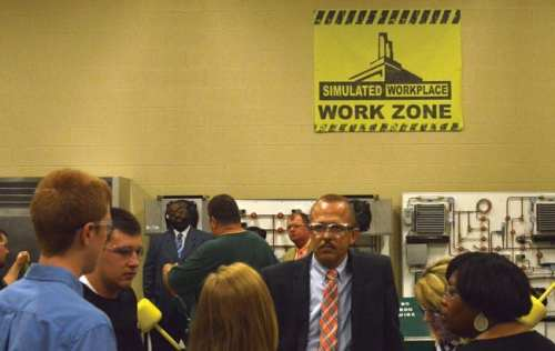 "people standing around in area labeled ""Simulated Workplace Work Zone"" wearing safety goggles"