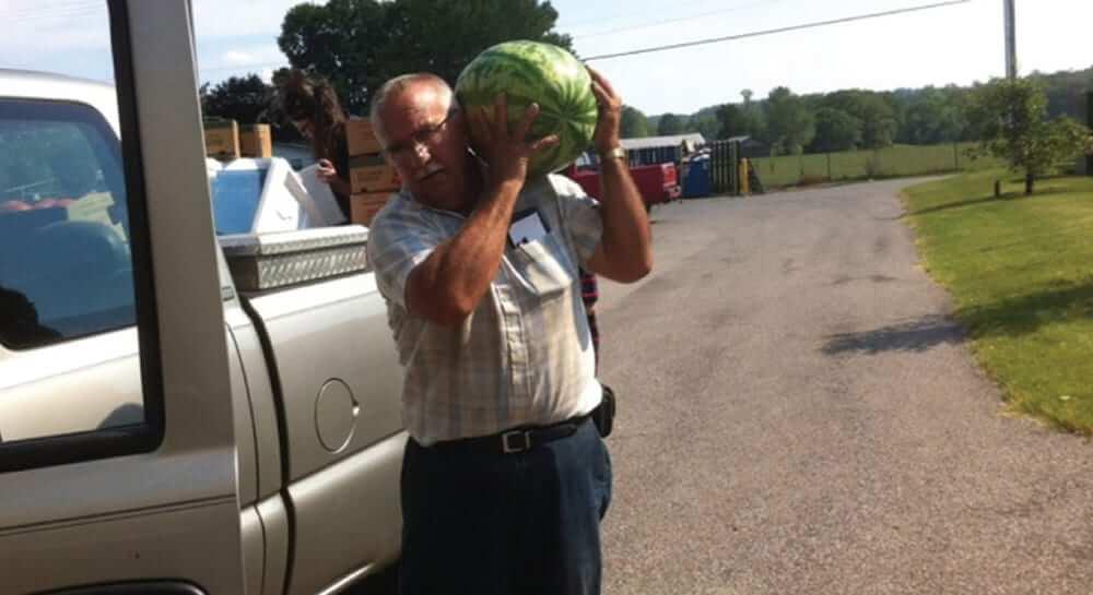 Farmer carrying watermelon.