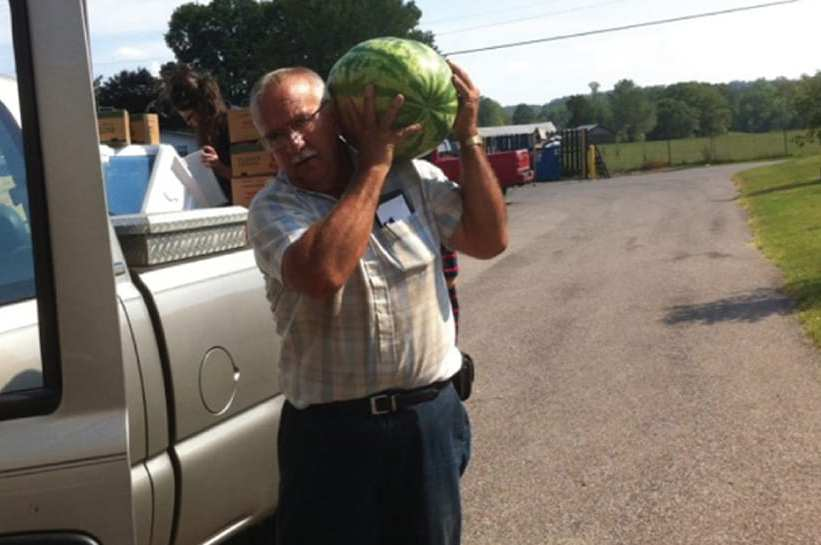 Farmer carrying watermelon.