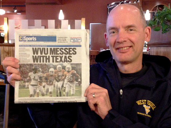 Dave holding paper after WVU beat Texas