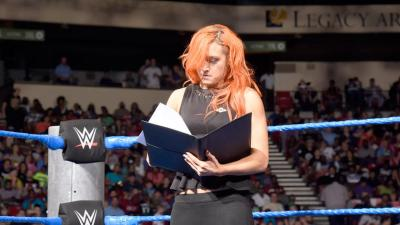 She returns to the ring to sign the contract, making their No Mercy match official.