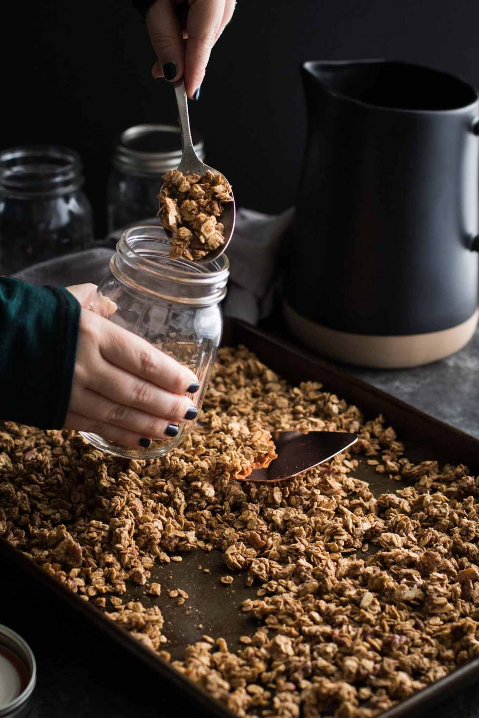 Spooning baked crunchy chai spiced granola from the pan into jars