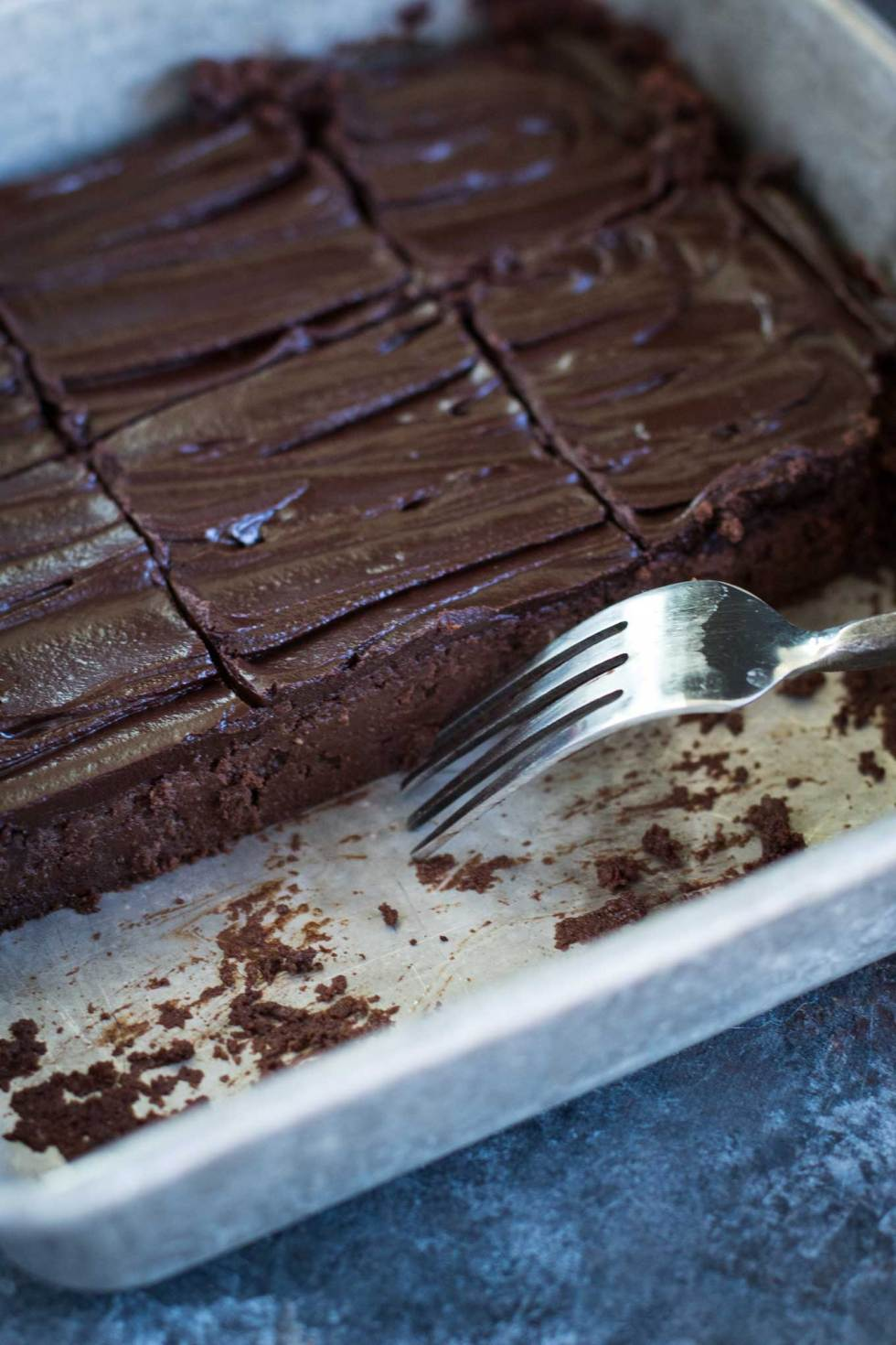 Close-up shot of half-full brownie pan with a fork resting in the pan and chocolate crumbs scattered
