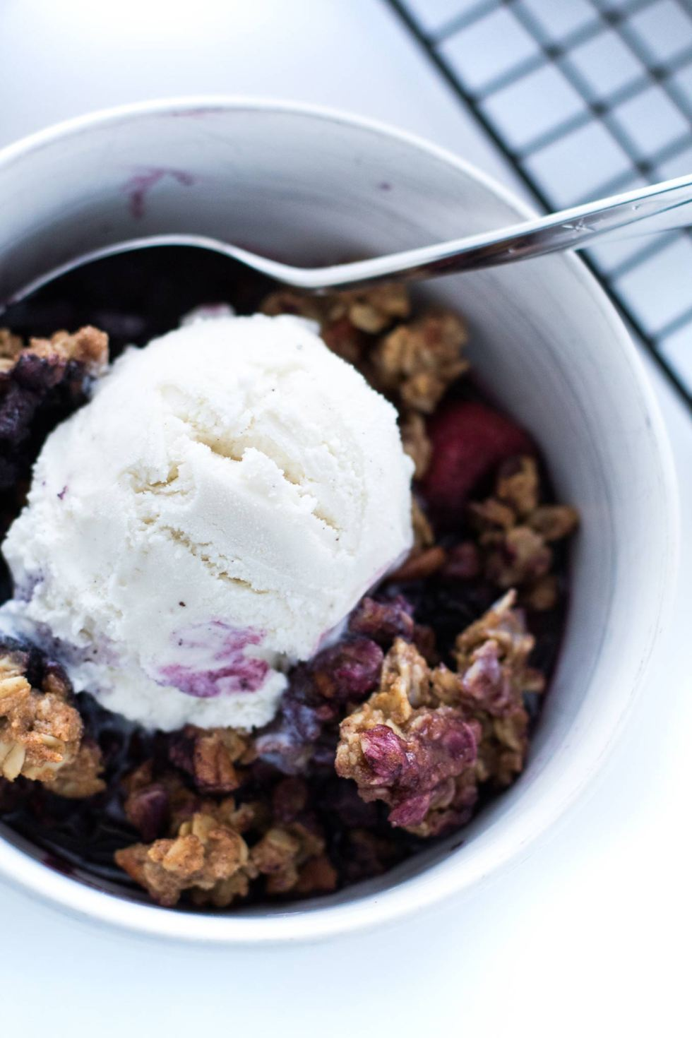 Overhead shot of frozen berry crumble with a scoop of vanilla ice cream melting into it.