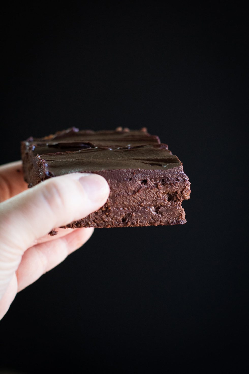 A hand holding up a dark chocolate cheesecake brownie covered in chocolate ganache