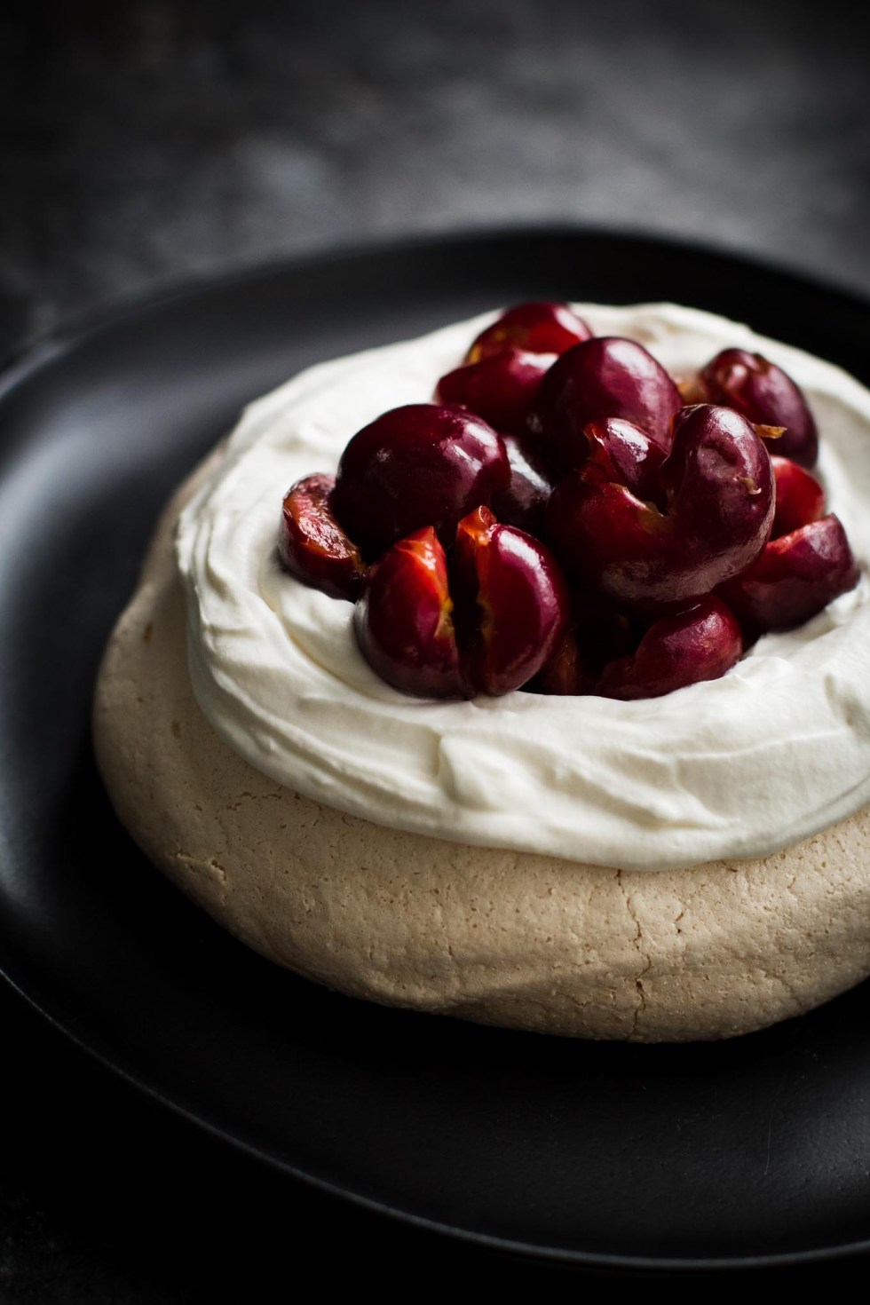 Close-up of pavlova with a pillow of whipped cream and scoop of bourbon cherries