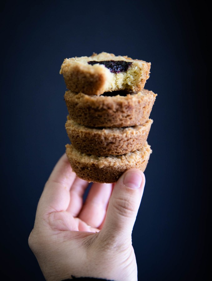 A stack of four earl grey shortbread cookies being held up to the light.
