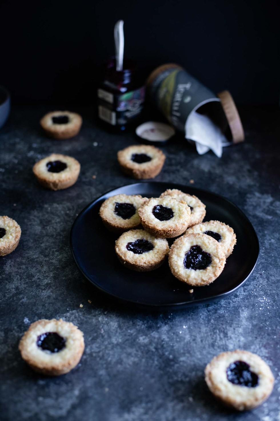 A black plate full of earl grey shortbread cookies with blackberry jam