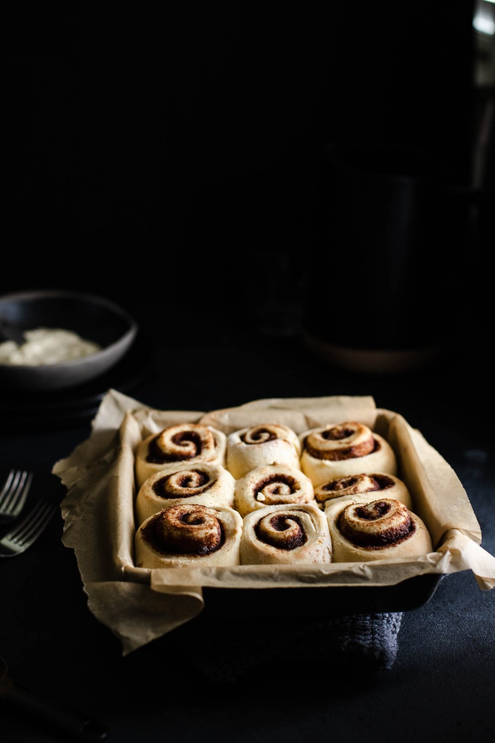 Browned cinnamon rolls resting in the pan after they've come out of the oven.