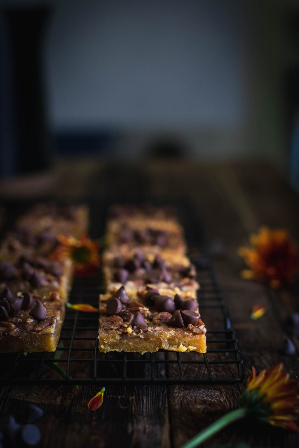 Pumpkin Pecan Toffee Bars cooling on a black cooling rack with orange flowers and chocolate chips scattered about