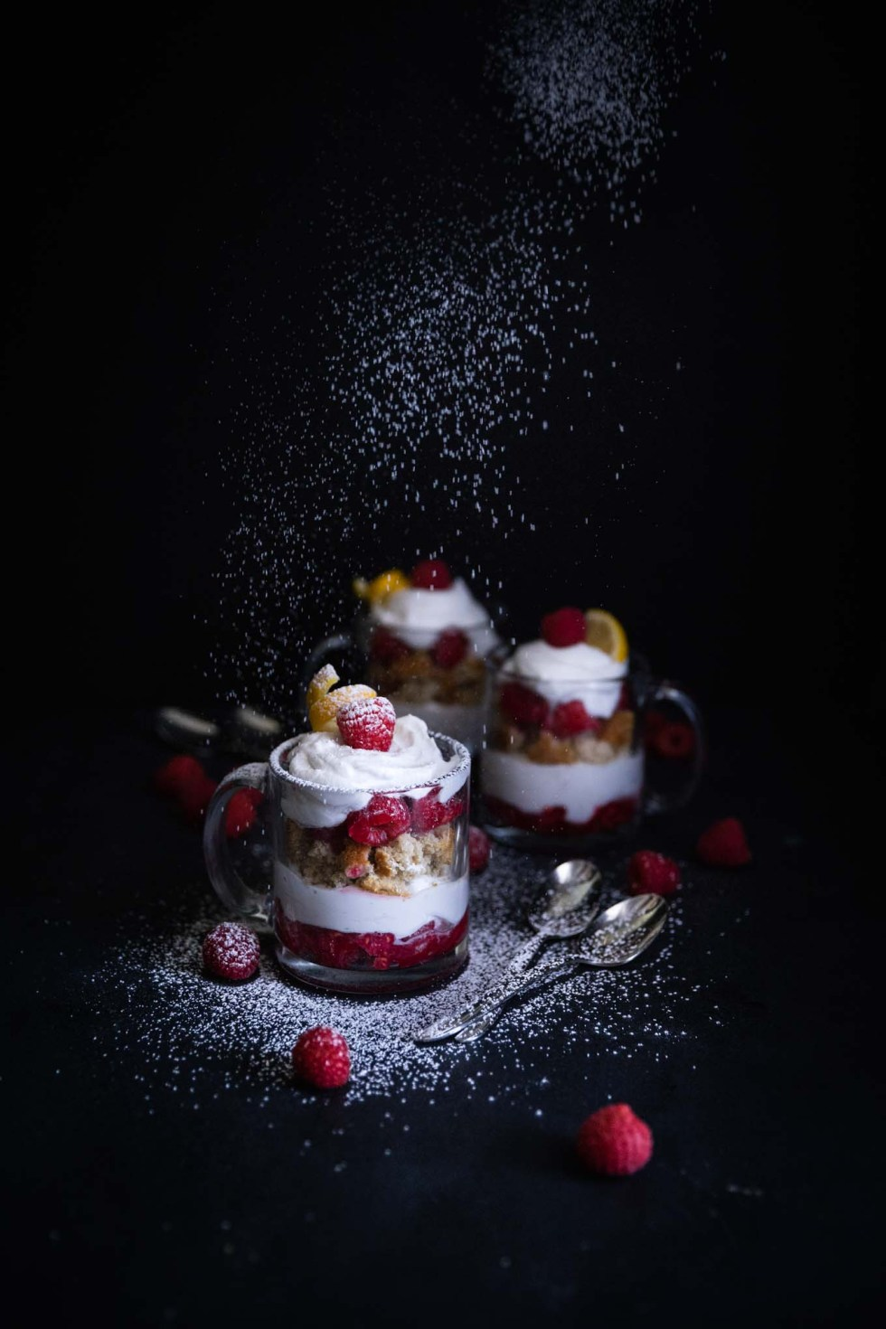 Dusting Raspberry Lemon Cake Trifles with powdered sugar