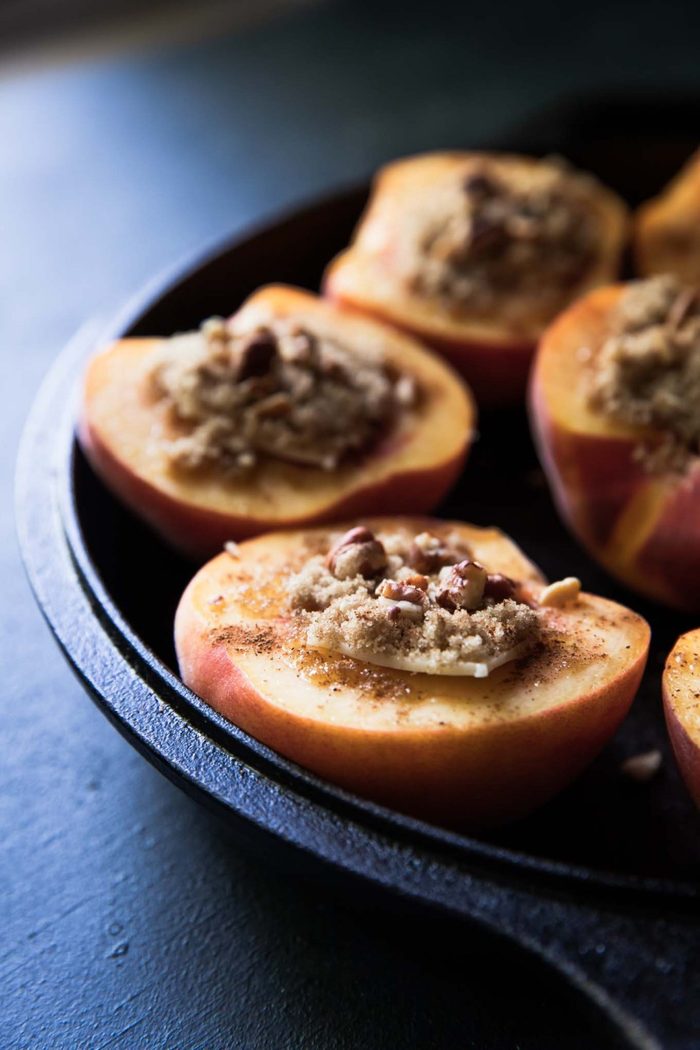 Peach halves topped with a sliver of butter and sprinkles of brown sugar and cinnamon.
