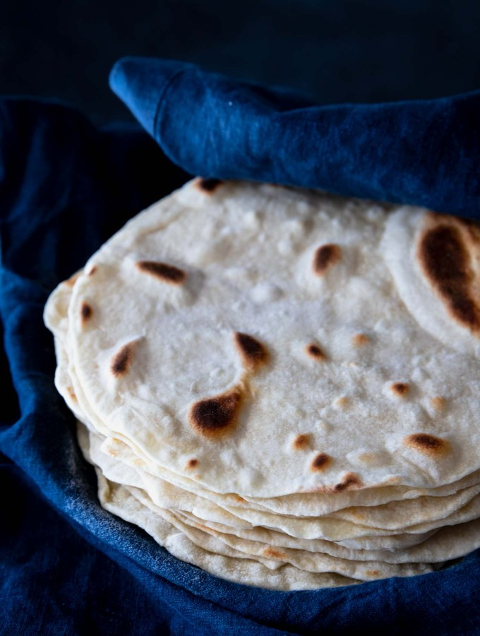 A stack of cooked, browned flour tortilla in a blue towel.