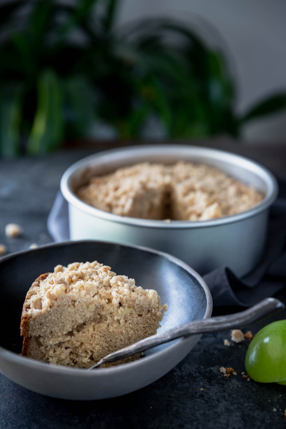 Overhead shot of an apple crumb cake with one slice pulled to a black bowl