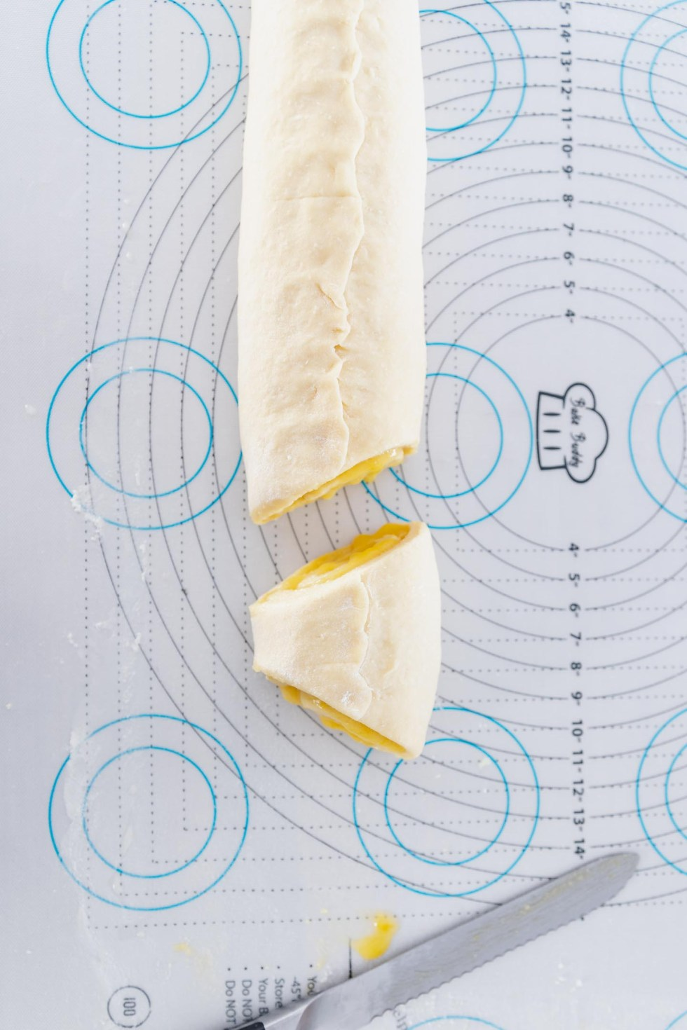 Log of rolled up sweet rolls being sliced.