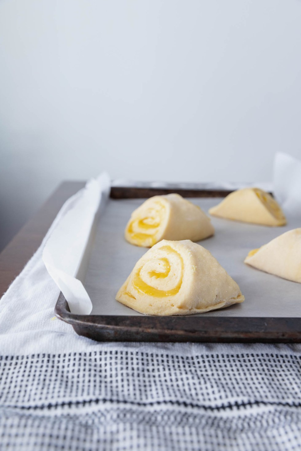 Pyramids of meyer lemon sweet roll on parchment lined sheet.