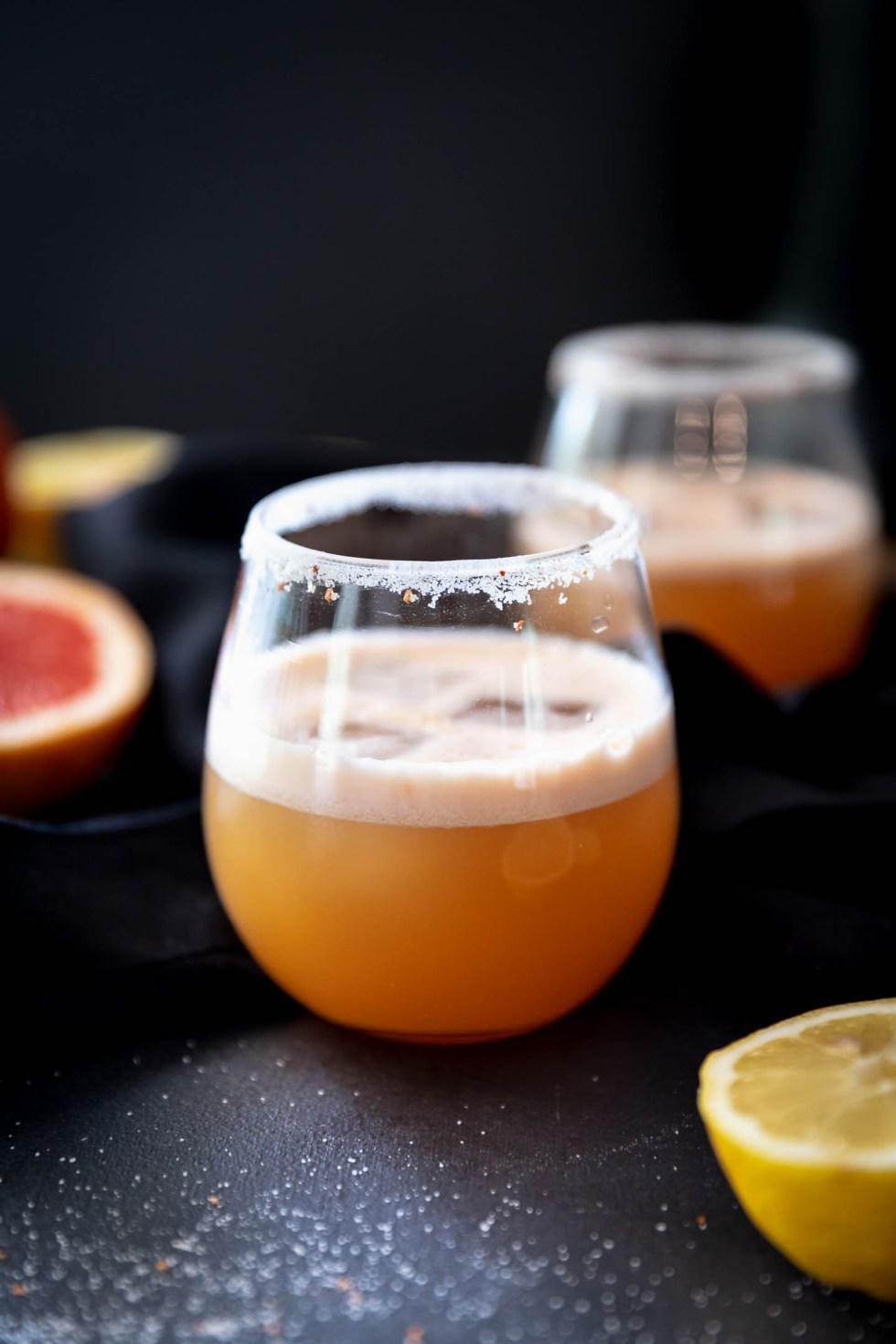 Stemless wine glass with grapefruit margarita and a tajin sugar rim