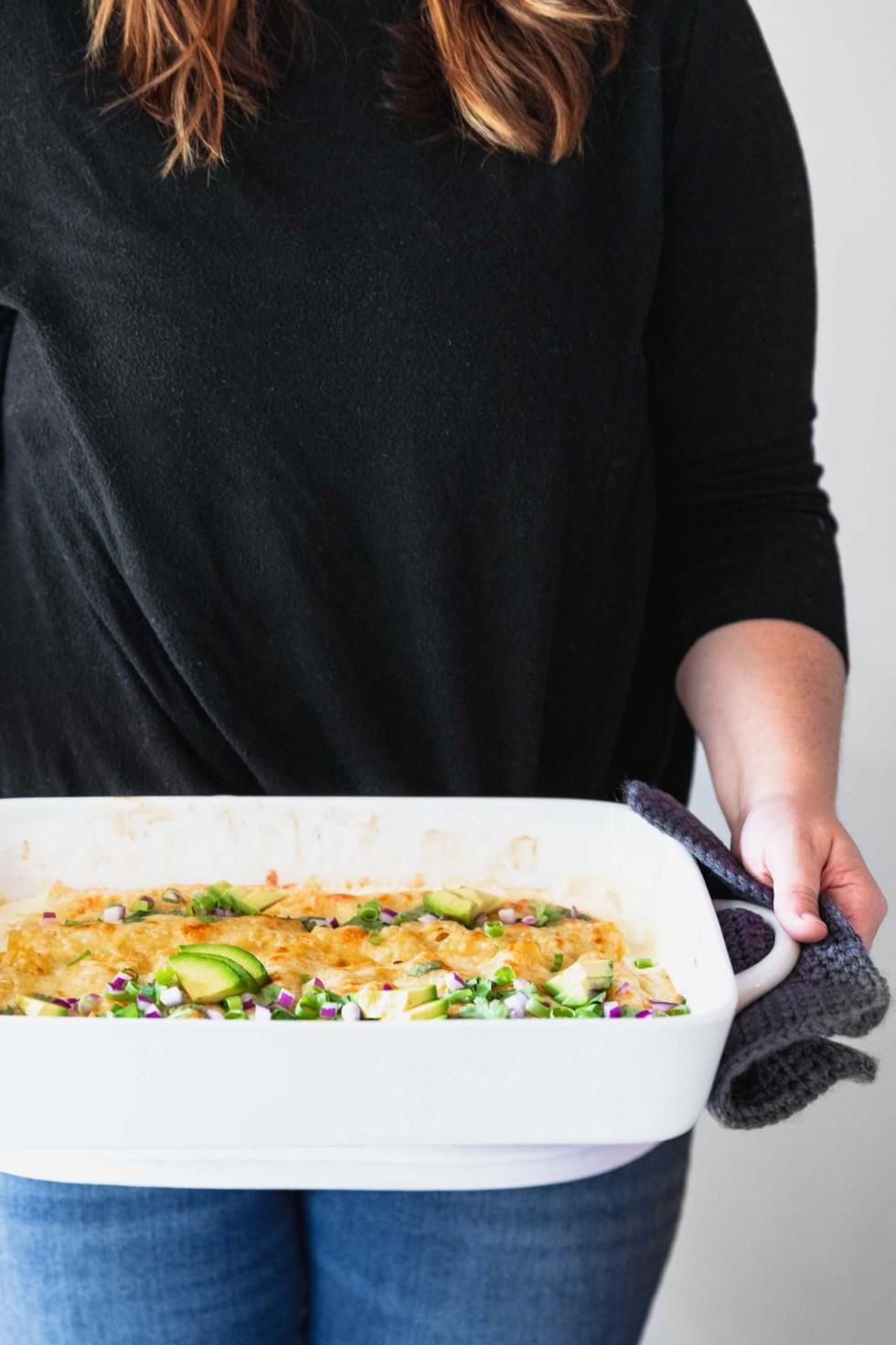 Girl delivering casserole of white chicken enchiladas