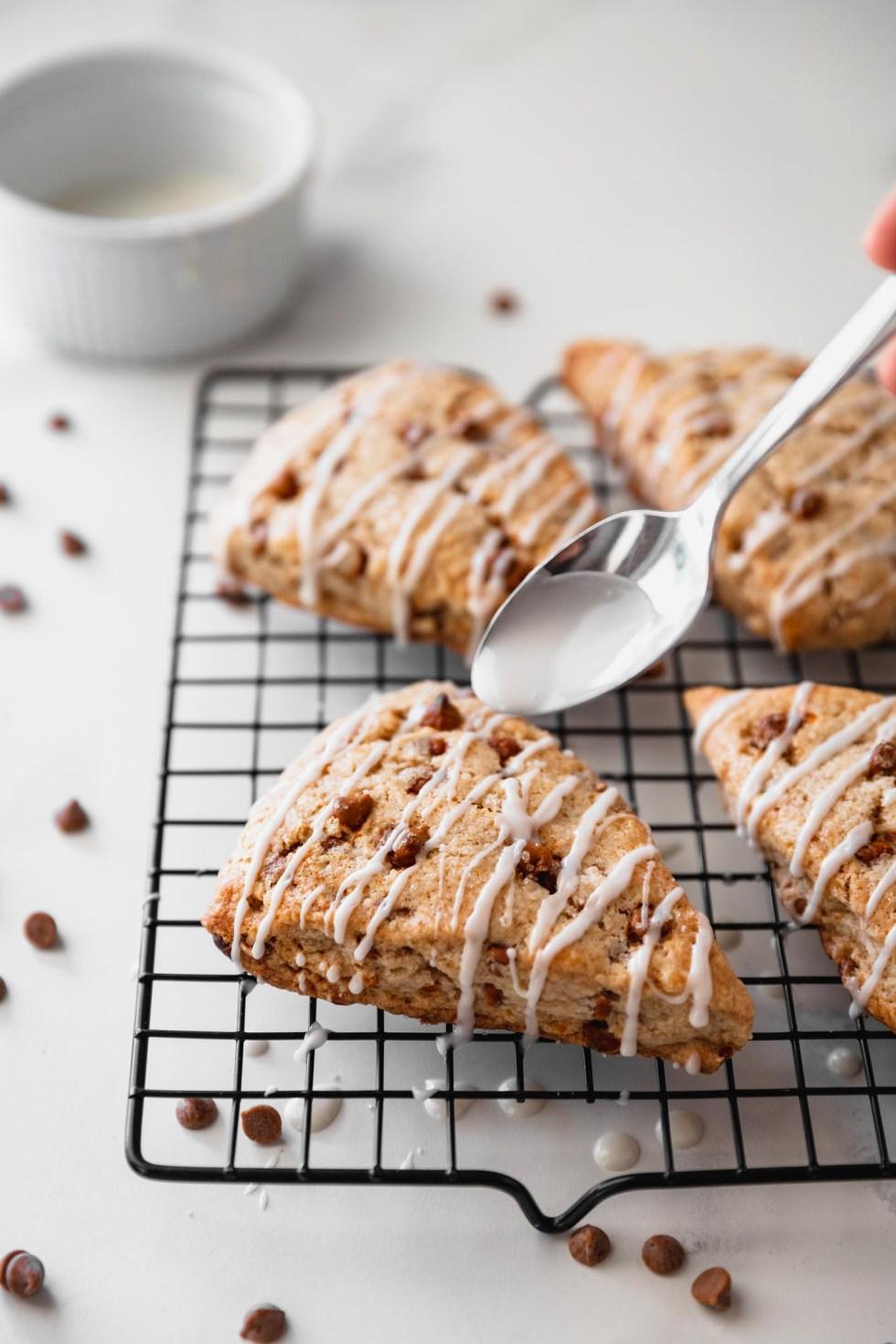 Silver spoon drizzling glaze over cinnamon scone
