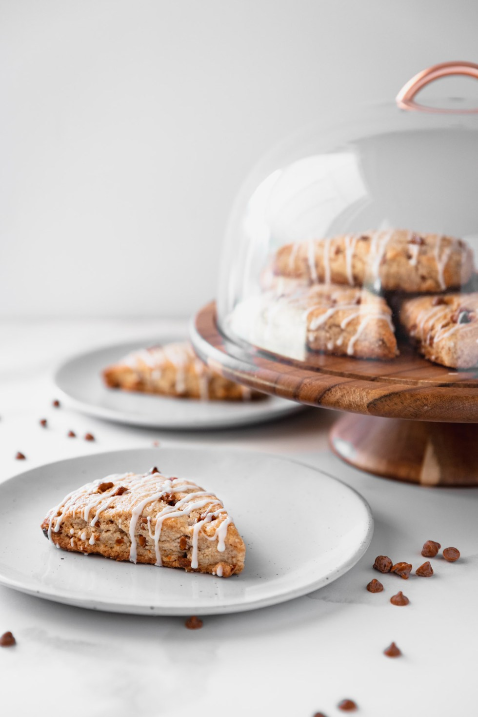 Cinnamon chip scone on a small plate with extras on a cake platter