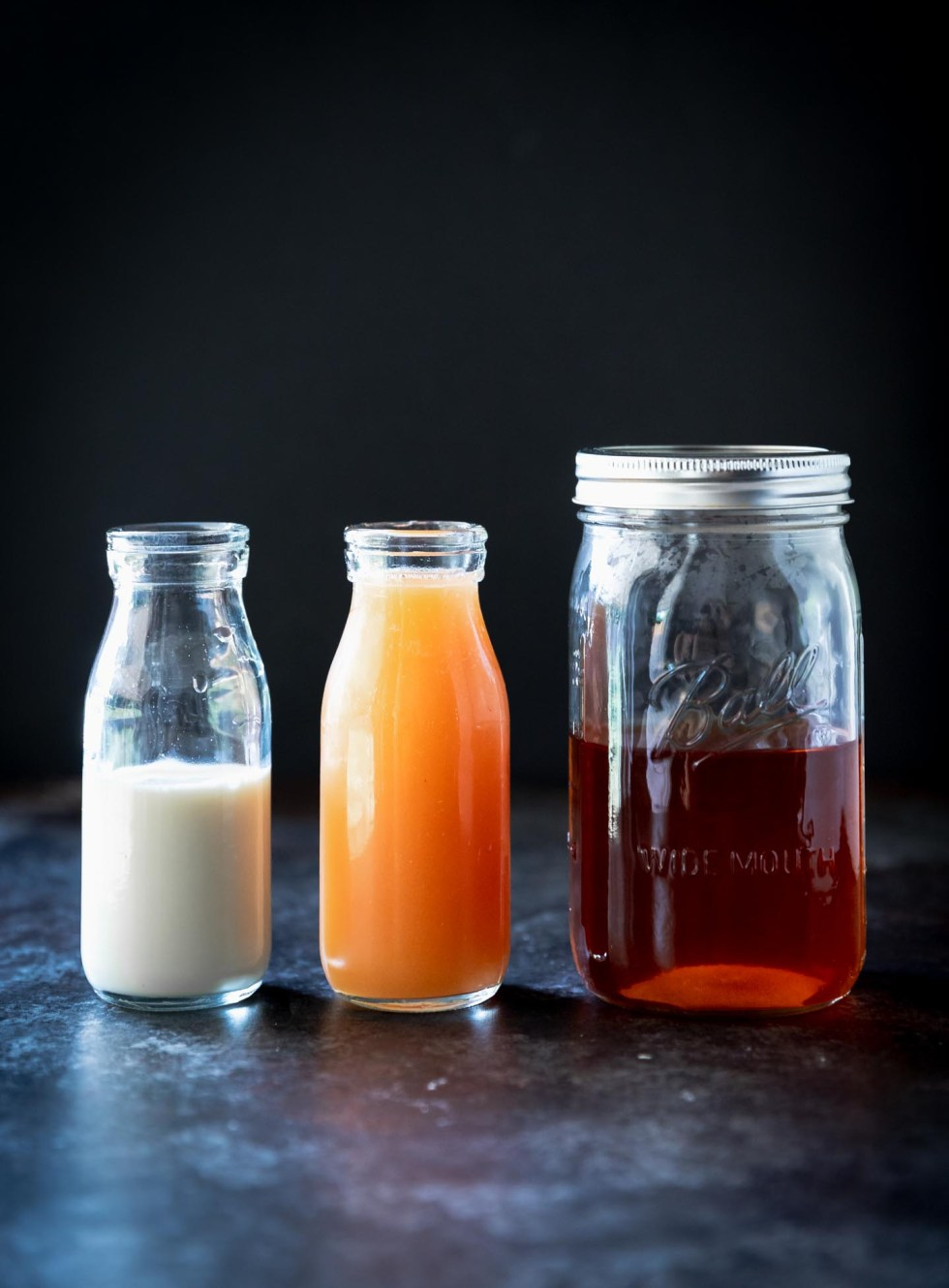 Three jars side-by-side of tea, guava, and milk