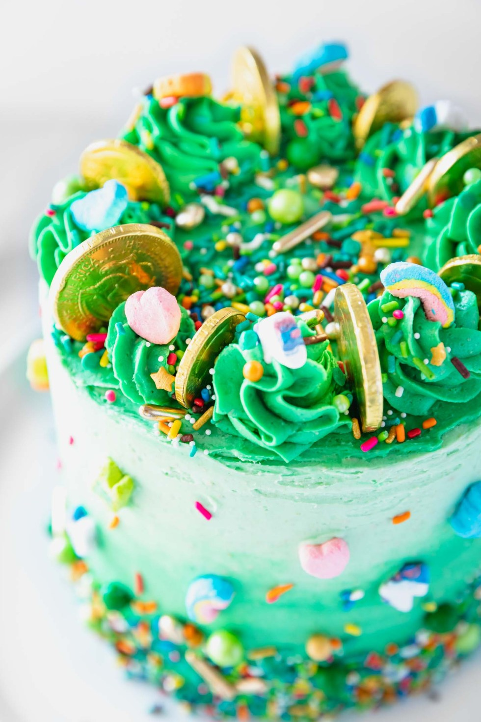 Close up of green buttercream swirls on top of a st. patrick's day ombre cake.