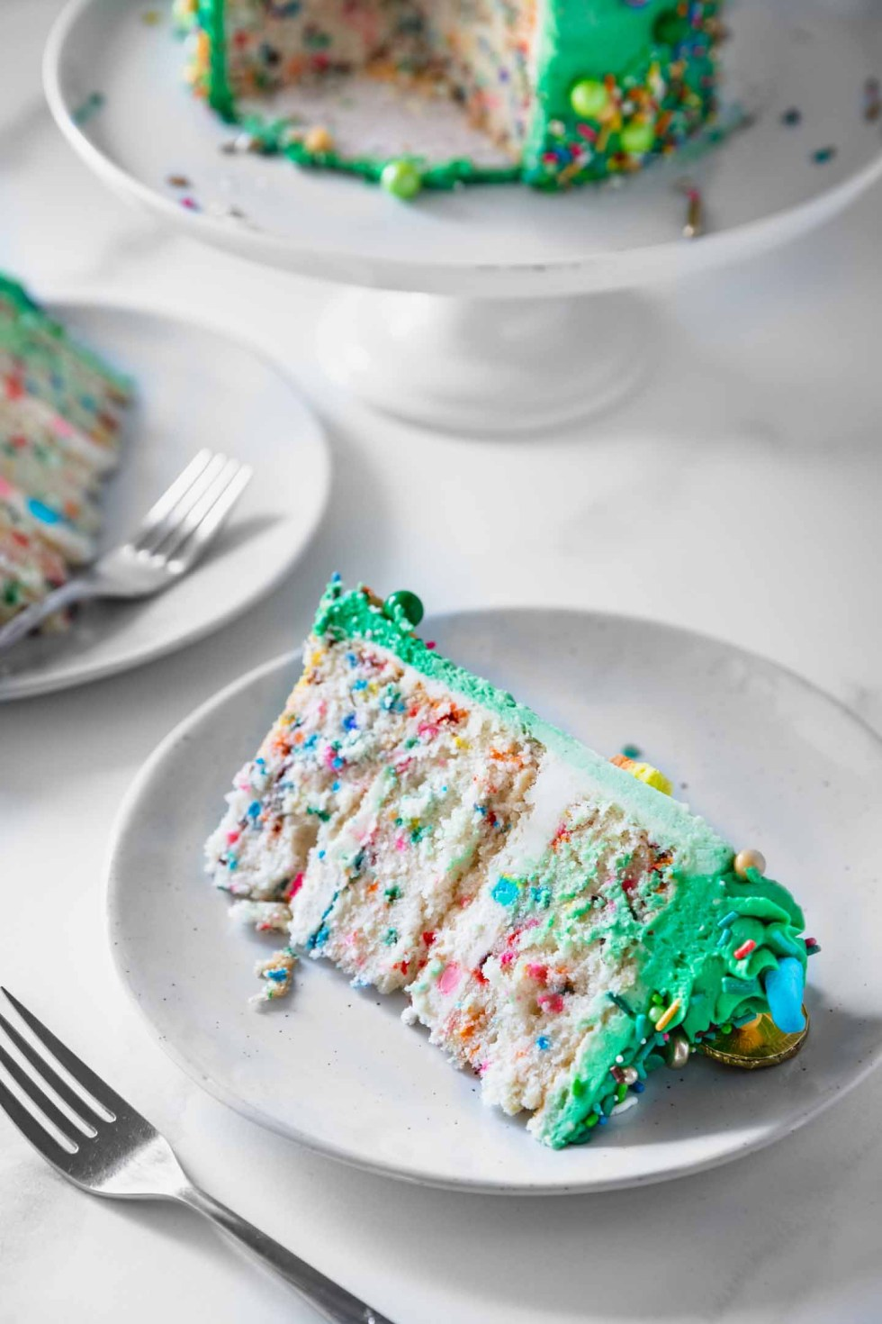 Close-up of a cake slice on a white plate with lucky charms marshmallows mixed in.